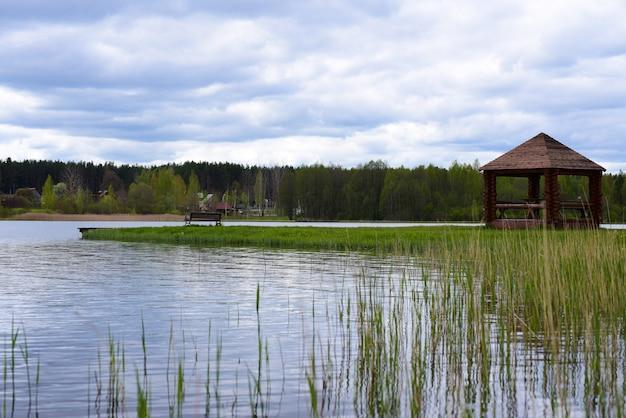 森の湖の岸にベンチが付いている木のあずまや