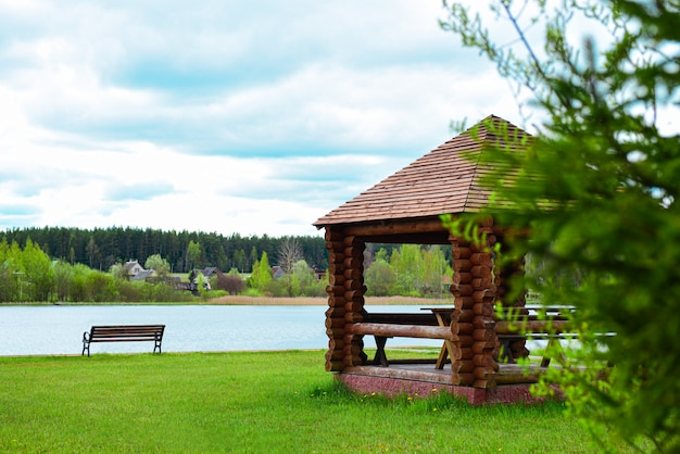Wooden arbor with a bench on the shore of a forest lake