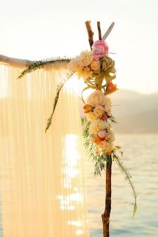 夕暮れ時の結婚式用の木製アーチ