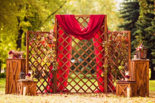 Wooden arch on the wedding ceremony with a red fabric and grape branches