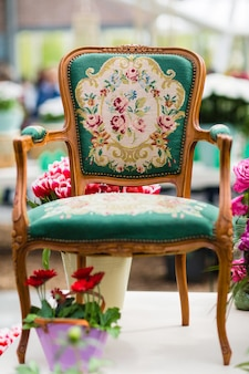 Wooden arm chair with fabric upholstery and flowers in background