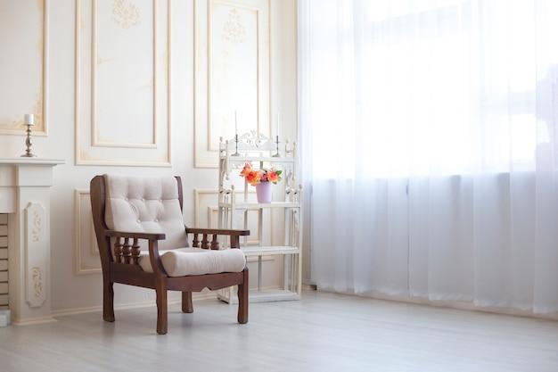 나무 안락 의자는 창 옆의 흰색 방에 서 있습니다. 빈티지 가구. 창문이있는 방의 인테리어