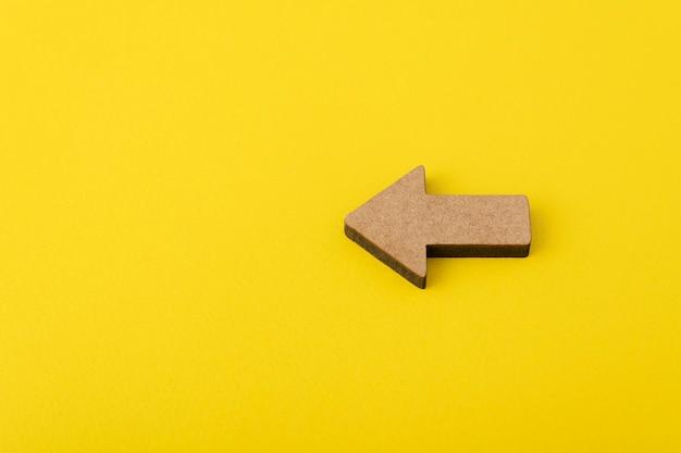 黄色の背景に木製の矢印。方向指示器。