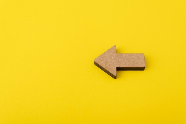 Wooden arrow on yellow background. direction indicator.