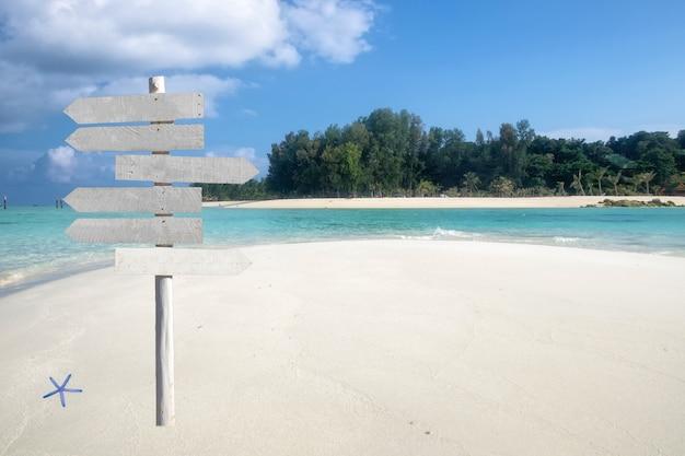 Деревянная вывеска стрелки на красивом тропическом море с белым пляжем