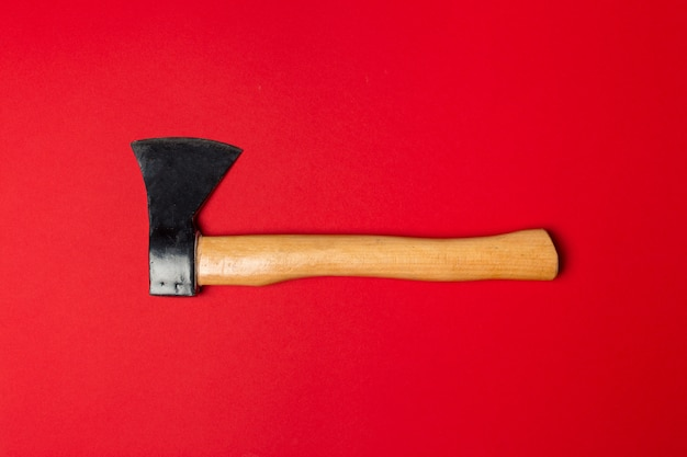 Wooden ax on bright red  top view