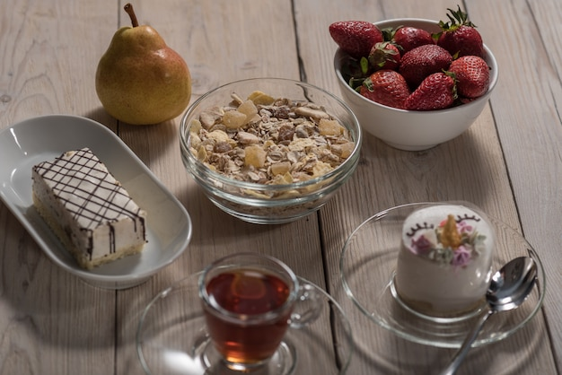 On a wooden background a children's cake, a plate with strawberries, pears, a cup of tea