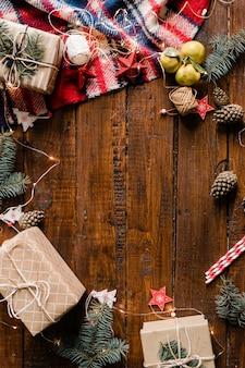 Деревянный фон в обрамлении упакованных подарочных коробок, гирлянд, елочных игрушек, шишек и хвойных деревьев.