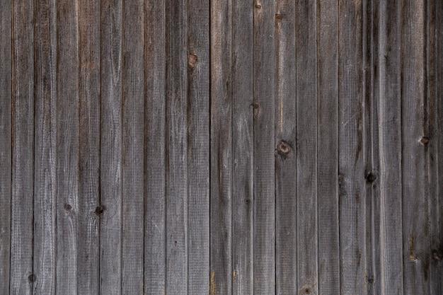 Деревянный фон из вертикально расположенных старых темных досок, текстура древесины