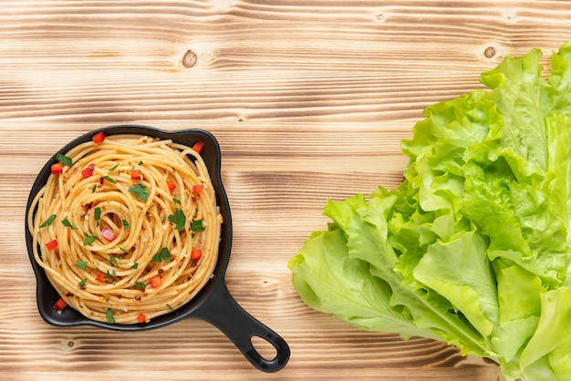 On a wooden background is a plate with pasta and herbs. copy  space.