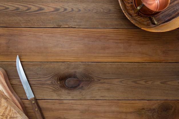 木製の背景。台所用品、木製皿、ナイフ。