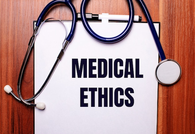 On a wooden background lies a stethoscope and a sheet of paper with the inscription medical ethics. flat lay. medical concept