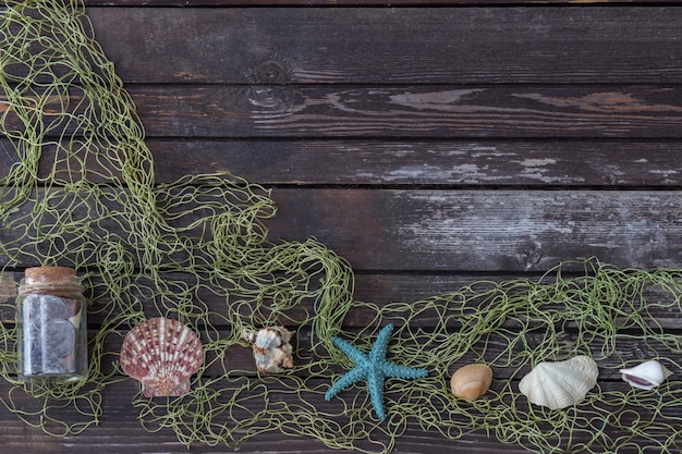 On a wooden background marine attributes: net, seashells, starfish, bottle with a message