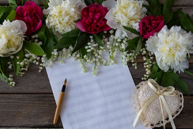 On a wooden background peonies and lilies of the valley, paper for notes