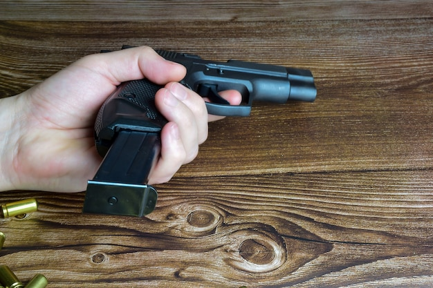 On a wooden background there are scattered cartridges as well as a hand holding a pistol