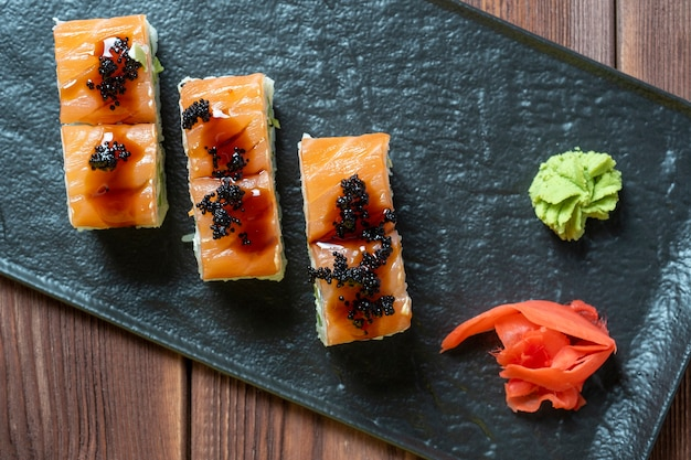 On a wooden background, there is a black textured plate with delicious rolls laid out. next to pickled ginger and spicy wasabi. japanese cuisine