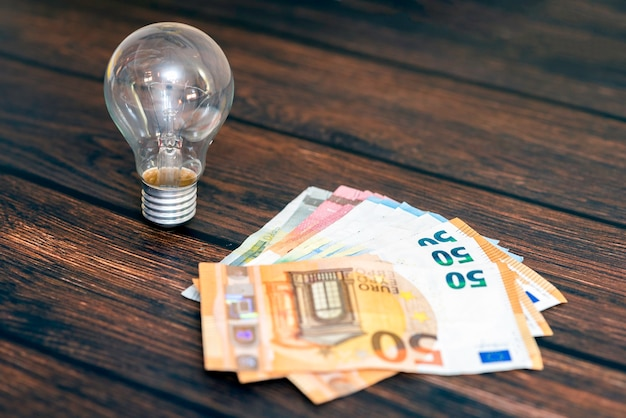 On a wooden background there is a light bulb and money in the form of several bills.