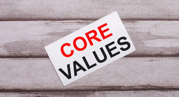 On a wooden background, there is a white card with red text core values