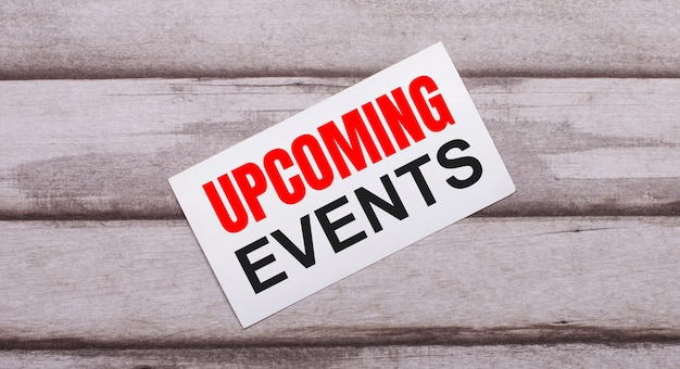 On a wooden background, there is a white card with red text upcoming events