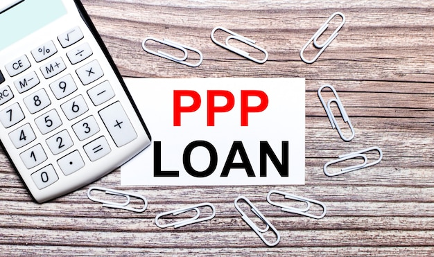 On a wooden background, a white calculator, white paper clips and a white card with the text ppp loan. view from above.