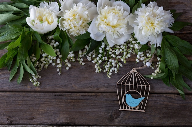 On a wooden background white peonies and lilies of the valley and a decorative wooden cage