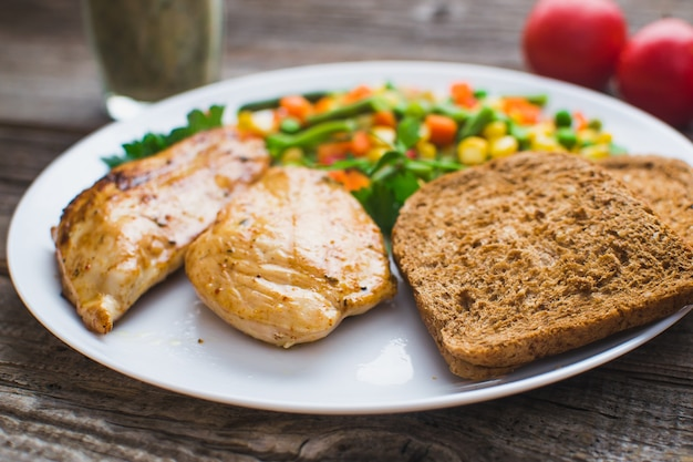 On a wooden background, white plate with breakfast, chicken breast and vegetables
