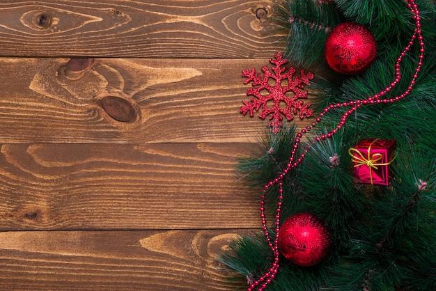 テキスト用のスペースで飾られたクリスマスツリーの枝と木製の背景。新年のコンセプト。スペースをコピーします。フラットレイを撮影するためのテーブルの表面。上面図。天然の生の鉋。