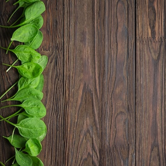 Wooden background with baby spinach leaves. copy space. healthy eating concept