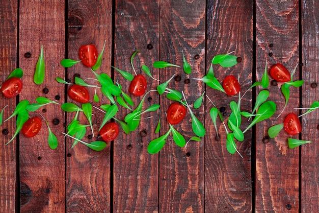 バジルの葉とチェリートマトの木製の背景。コピースペース、トップビュー。