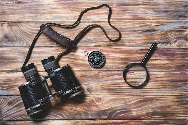 Wooden background with binocular, compass and magnifying glass