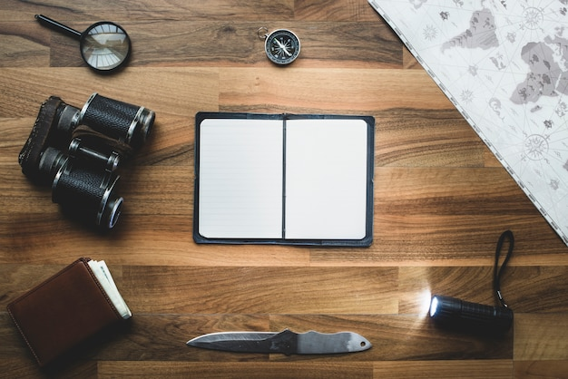 Wooden background with blank notebook and objects around
