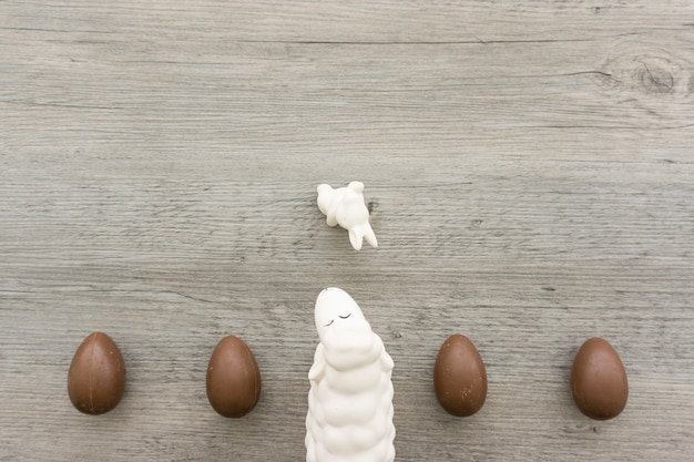 Wooden background with chocolate eggs and sheep for easter day