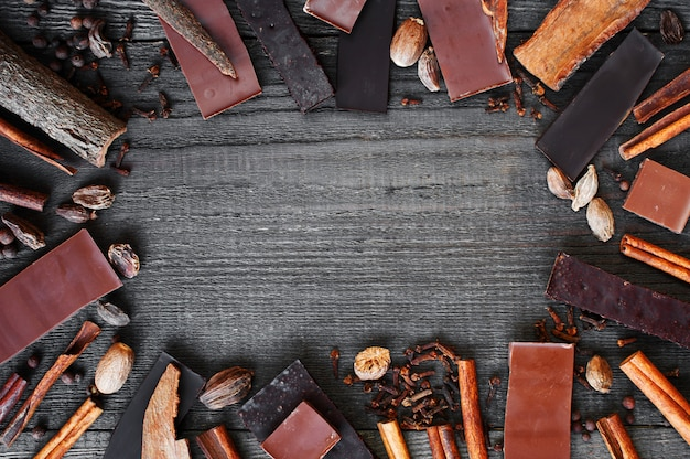 Wooden background with chocolate and spices