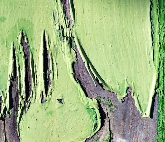 みじん切りの緑のペンキと木製の背景