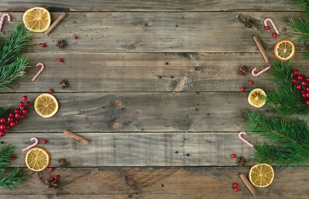 Wooden background with christmas decorations and dehydrated orange slices. top view.