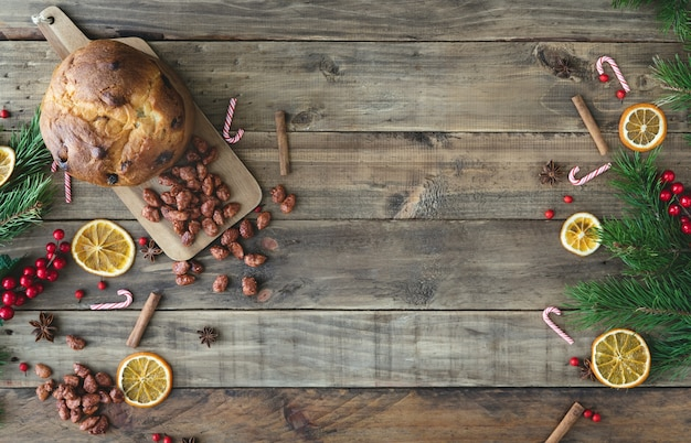 Wooden background with christmas decorations and dried orange slices and panettone. top view.