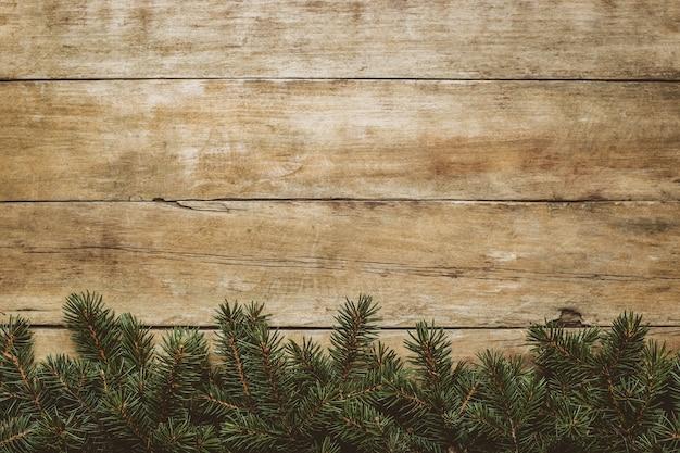 Деревянный фон с ветвями елки и снегом. рождественское понятие. баннер. плоская планировка, вид сверху.