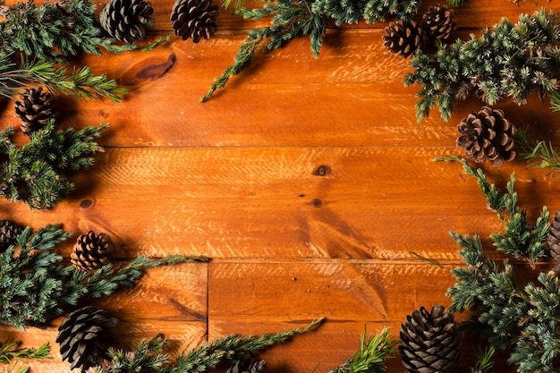Wooden background with christmas tree cones frame