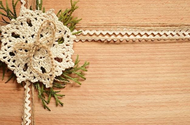 Wooden background with crochet lace and thuja branches