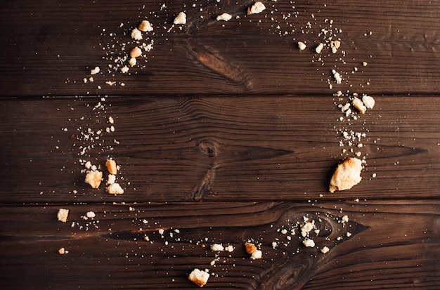 Wooden background with crumbs from cookies in the form of a circle, copy space