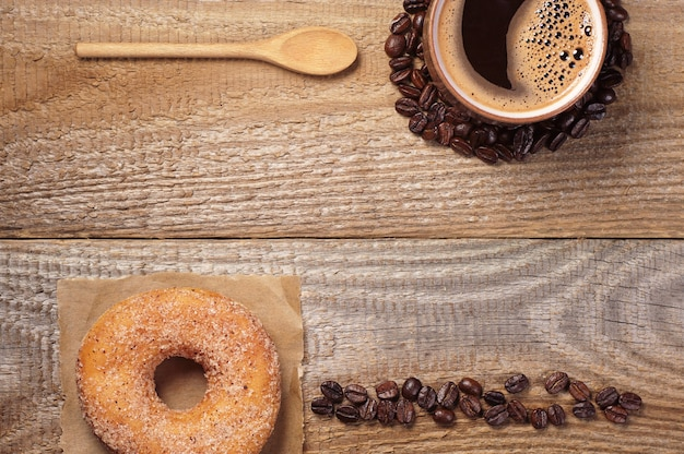 Wooden background with cup of hot coffee and sweet donut, top view