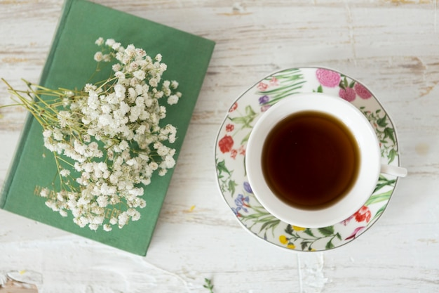 Wooden background with cup of tea, flowers and book