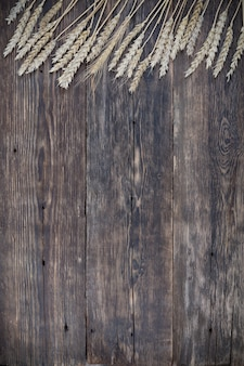 Wooden background with ears of wheat