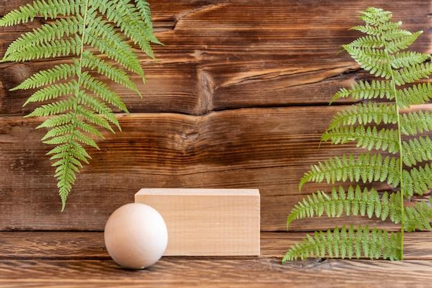 製品のショーケースのためのシダの葉と木製の表彰台と木製の背景。自然なアースカラーの構成。