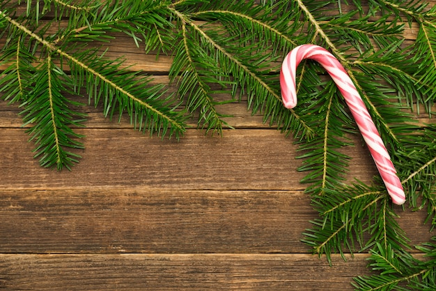 Wooden background with fir branches candy in the corner of the frame