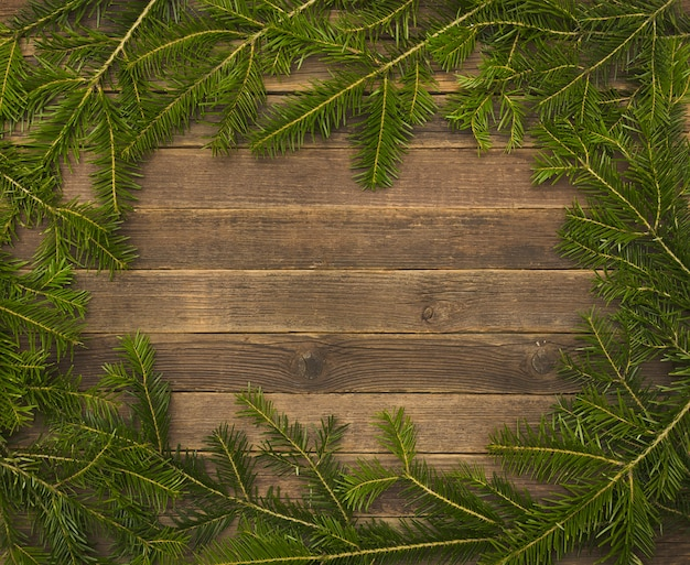 Wooden background with fir branches on the edge.