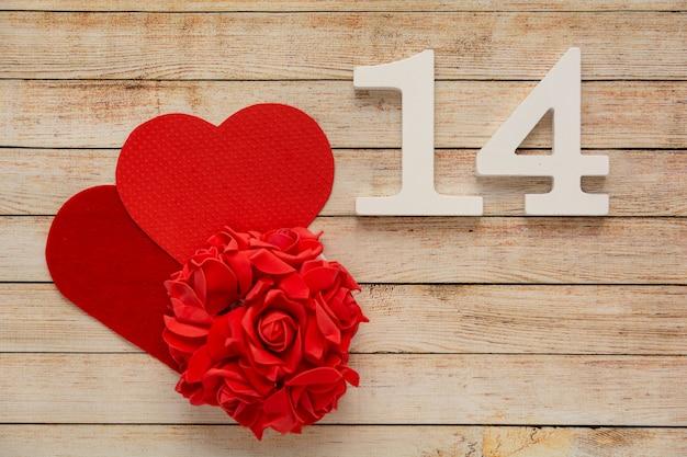 2月14日付の花、ハート、木製の番号を持つ木製の背景。バレンタインデーのコンセプト。