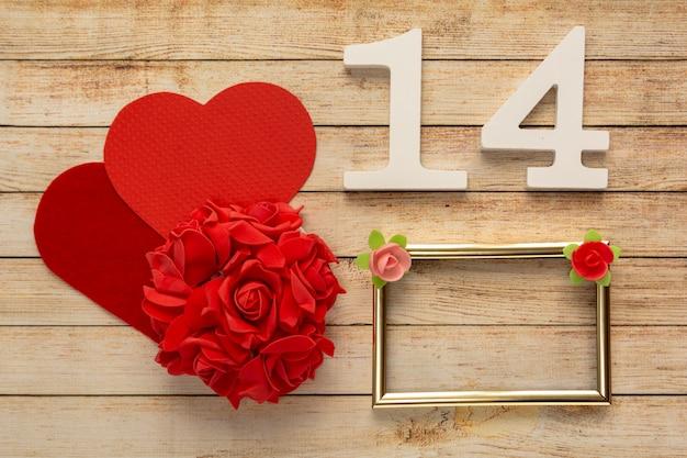 2月14日付の花、ハート、フレーム、木製の番号を持つ木製の背景。バレンタインデーのコンセプト。