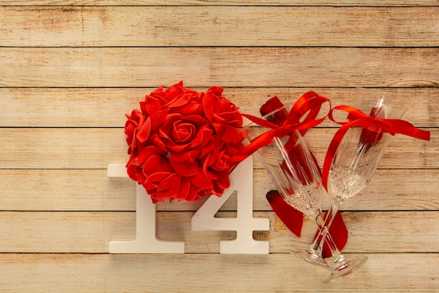 Wooden background with glasses of champagne, flowers and wooden numbers of dated 14 february. the concept of valentine day and restaurant romantic dinner