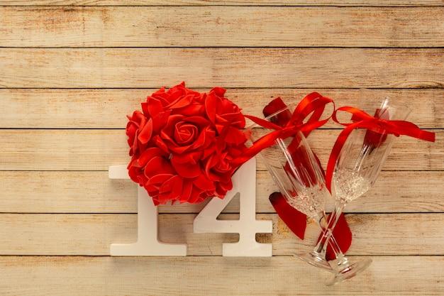 2月14日付けのシャンパン、花、木製の番号のメガネと木製の背景。バレンタインデーとレストランのロマンチックなディナーのコンセプト